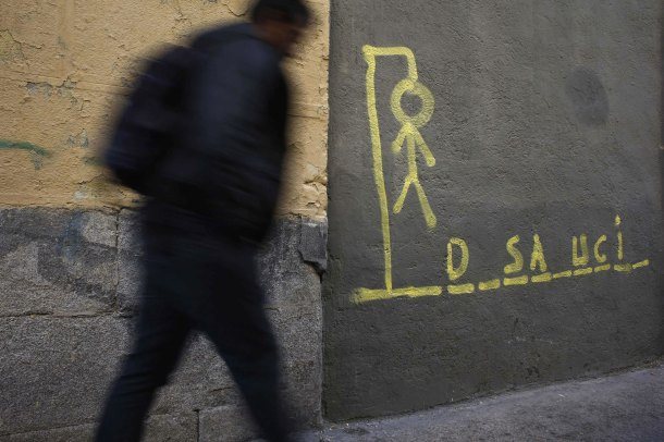 DOCU_GRUPO A man walks past a drawing of a hangman with the word eviction spelled out, on a street in central Madrid_desahucio