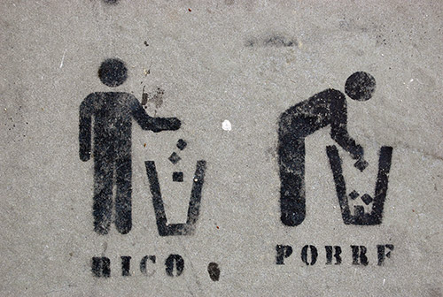 Stencil graffiti on a cement wall; two figures, both standing at garbage cans. One, labeled