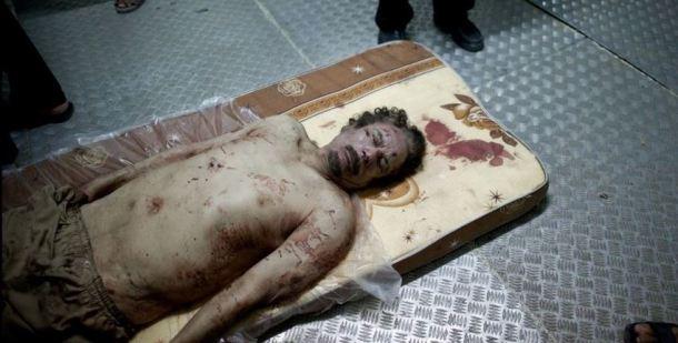 Tras ser asesinado, el cuerpo de Muamar el Gaddafi yace sobre un colchón en la cámara frigorífica de un mercado de verduras cerca de una mezquita en las afueras de Misrata. 21 de octubre de 2011 | Foto: Remi Ochlik
